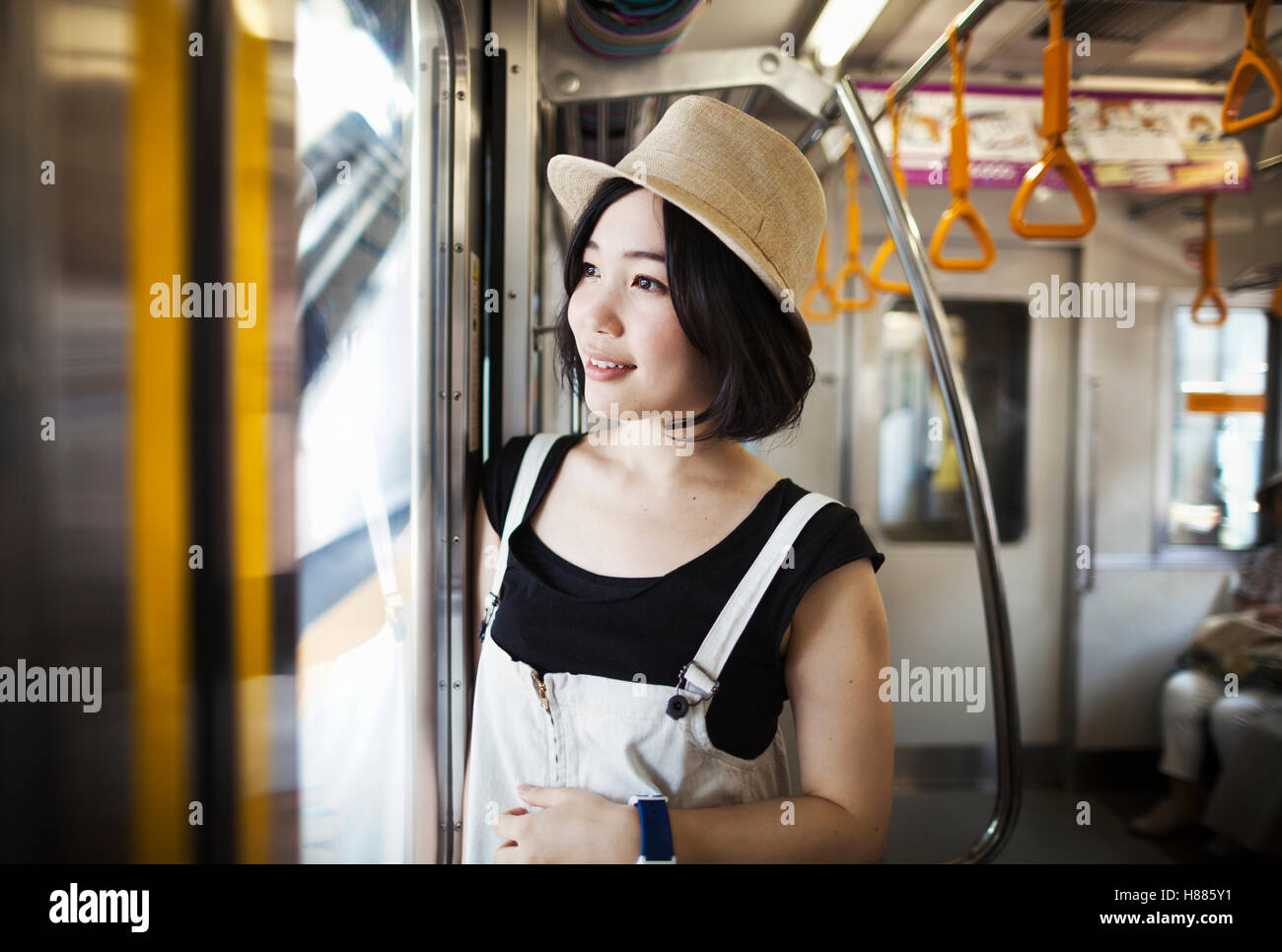 Young woman wearing a hat traveling on a train. - Stock Image
