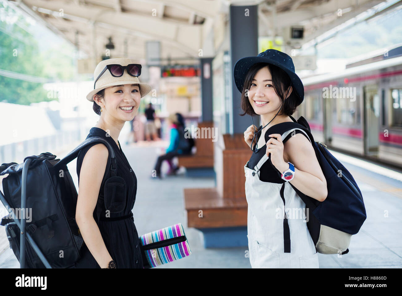 Two young women standing on a platform at a railway station. - Stock Image