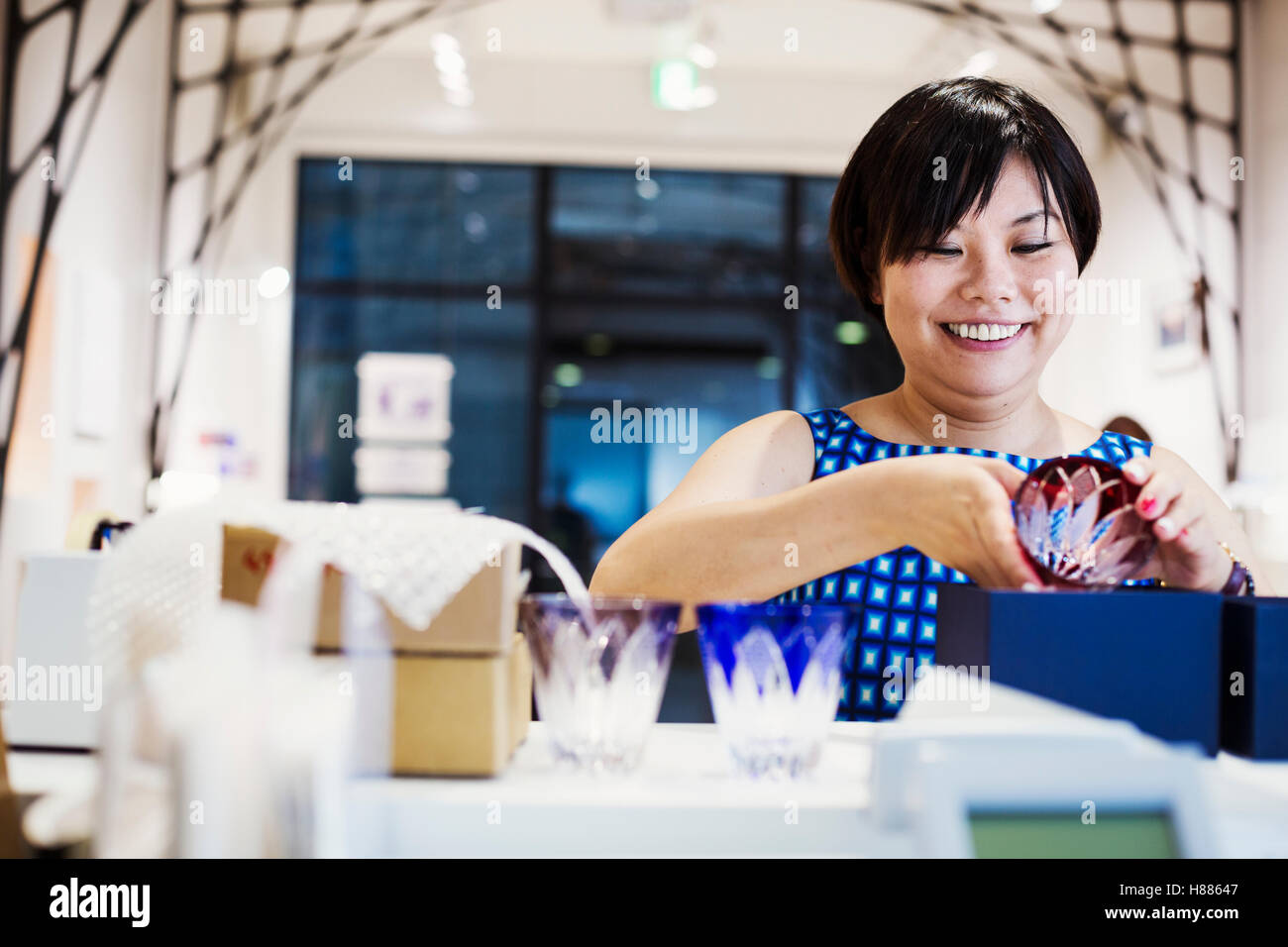 Saleswoman in a shop selling Edo Kiriko cut glass in Tokyo, Japan. - Stock Image