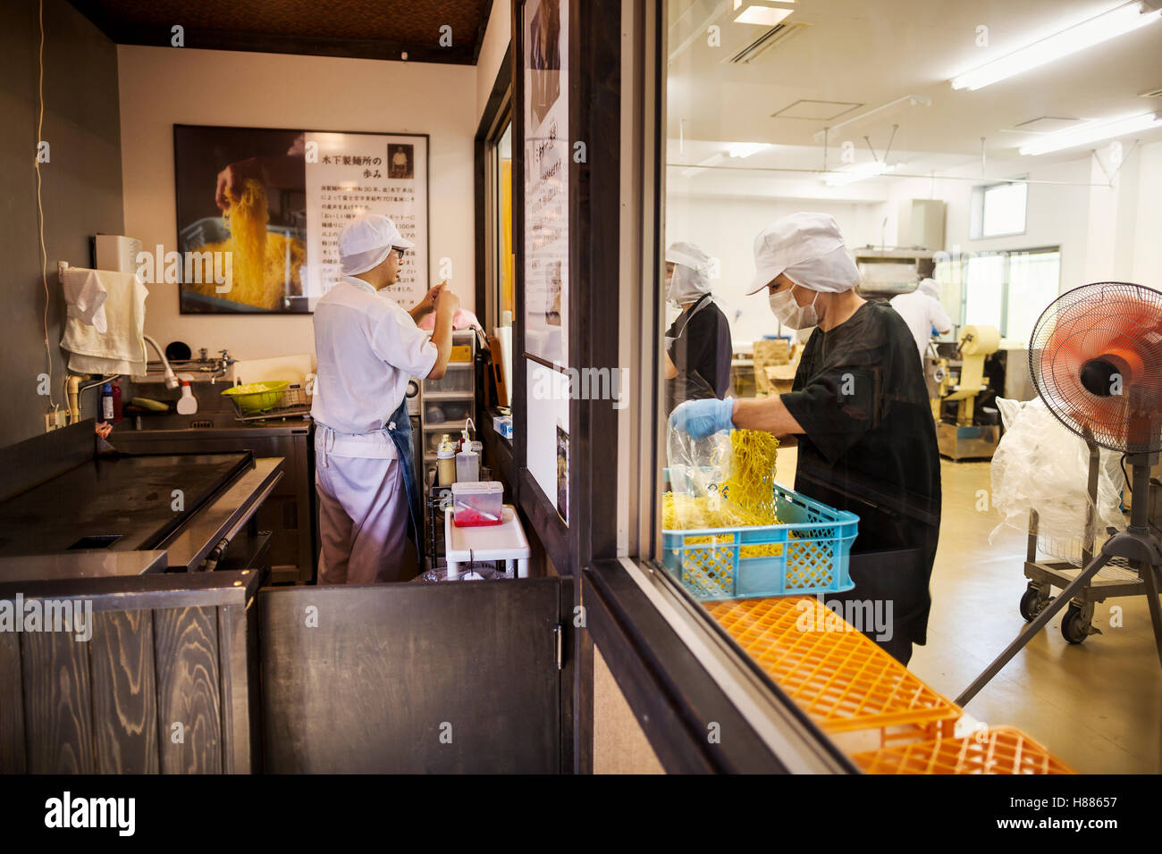 Factory production unit and commercial  kitchen serving a noodle shop. People working and a chef at a stove. - Stock Image