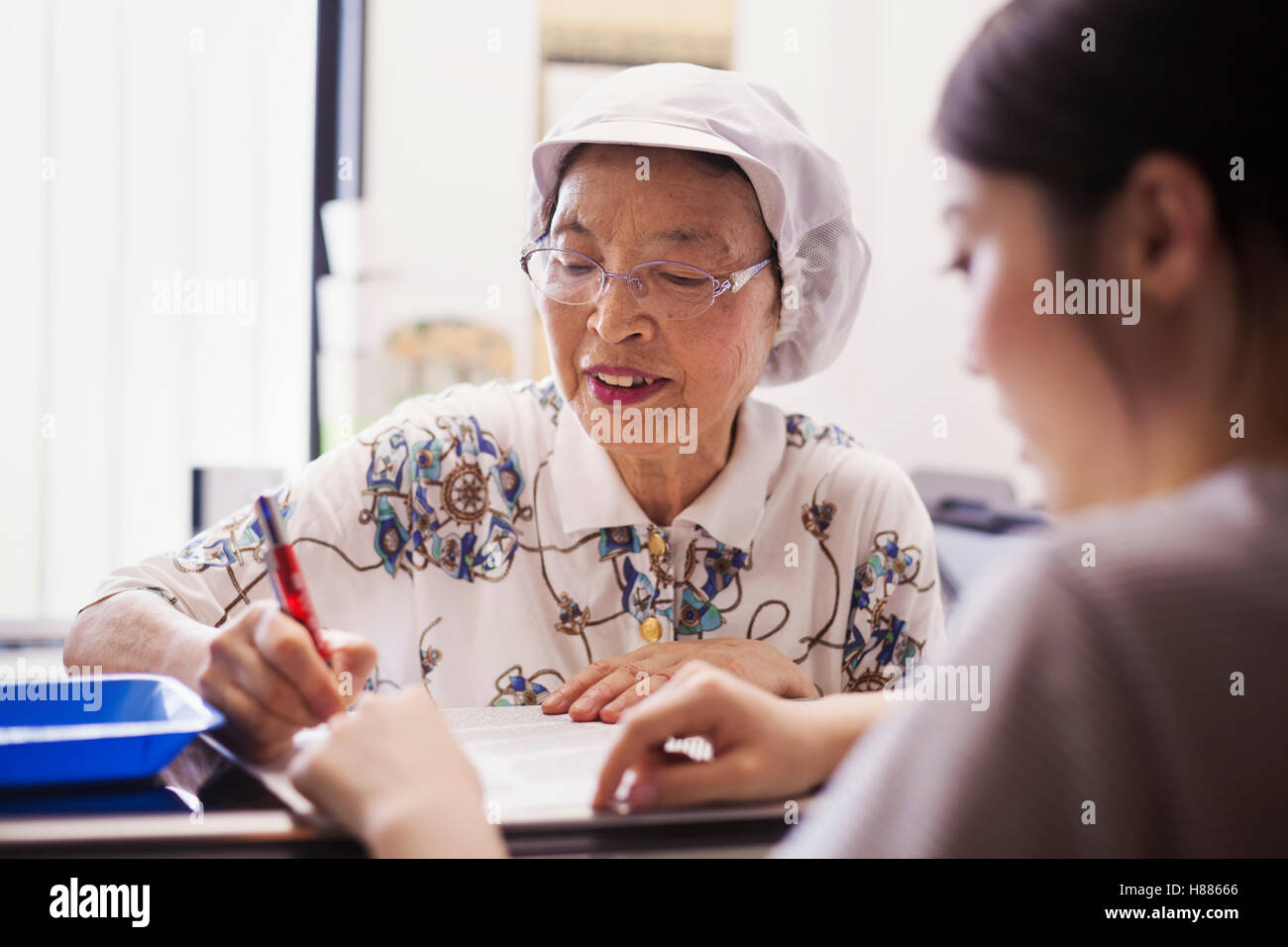 A mature woman at a desk in the office of a fast food unit and noodle production factory. - Stock Image