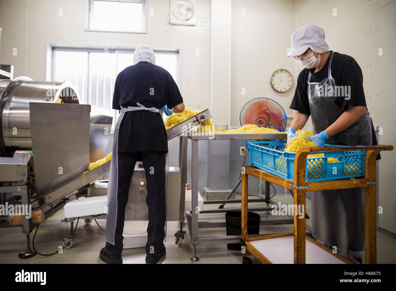 Workers in aprons and hats collecting freshly cut noodles from the conveyor belt to package and sell. - Stock Image