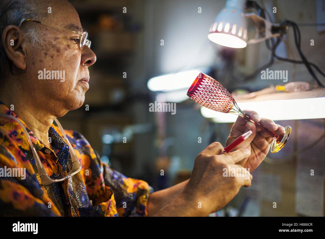 A senior craftsman at work in a glass maker's studio workshop. - Stock Image