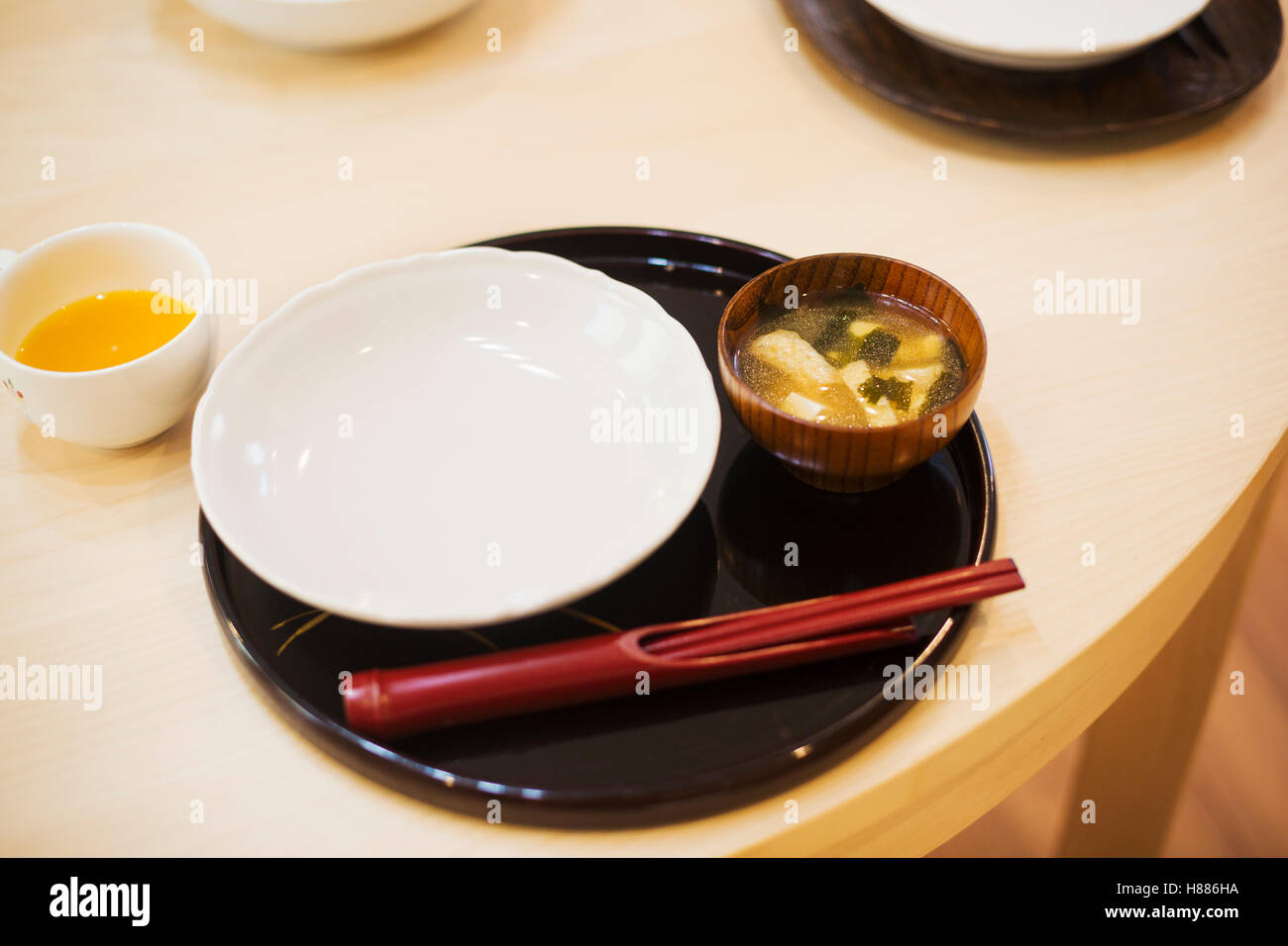 Family home. A table place set for a meal. Mat, bowl and chopsticks. - Stock Image