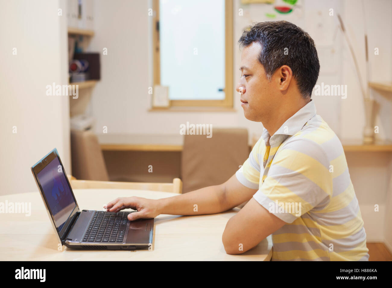 Family home. A man seated using a laptop working from home or dealing with online emails or business, administration, - Stock Image