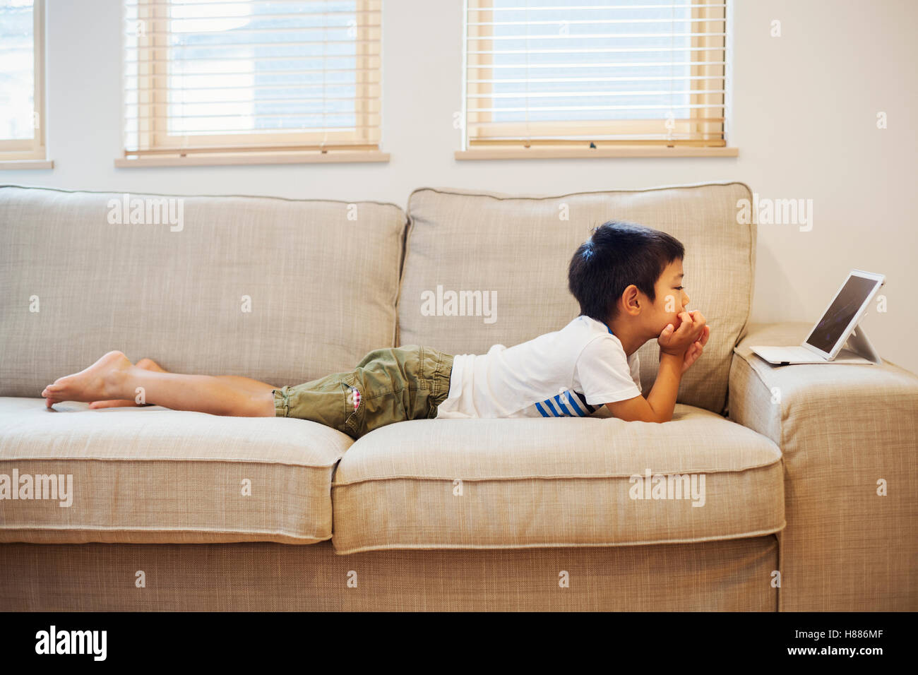 Family home. A boy lying on a sofa watching a digital tablet. - Stock Image