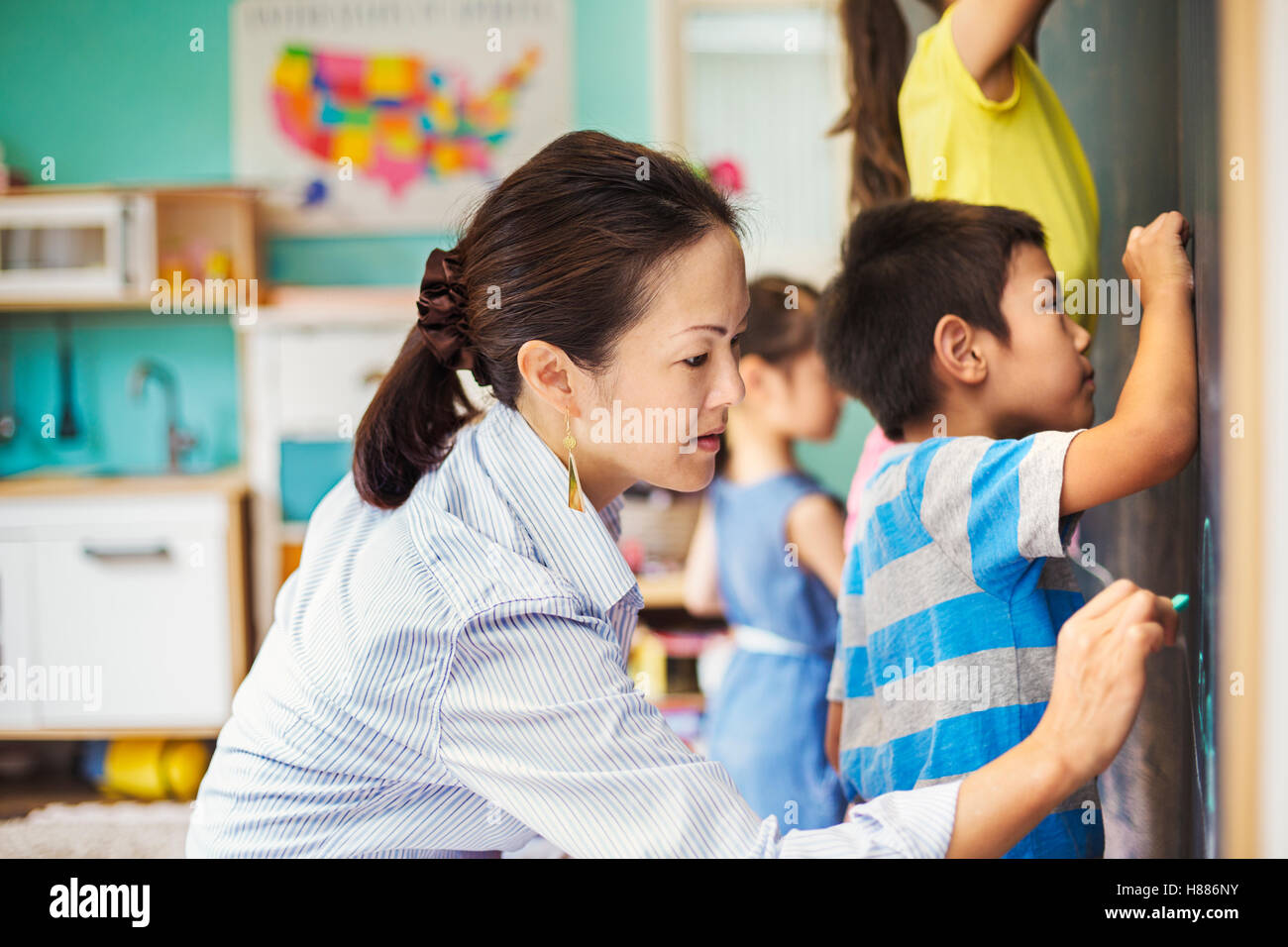 A group of children writing on the chalkboard with their teacher. - Stock Image