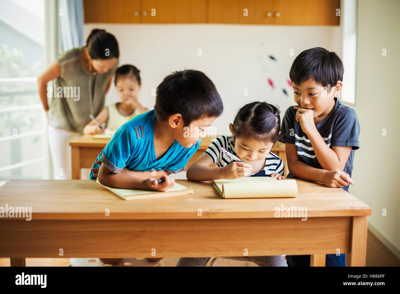 A group of children in a classroom with their female teacher. - Stock Image