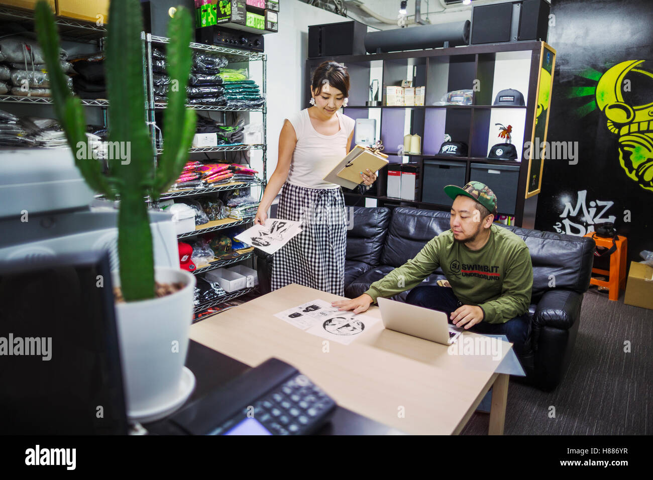 Design Studio. Two people in an office stockroom, looking at designs. Stock of clothes and hats on the shelves. - Stock Image