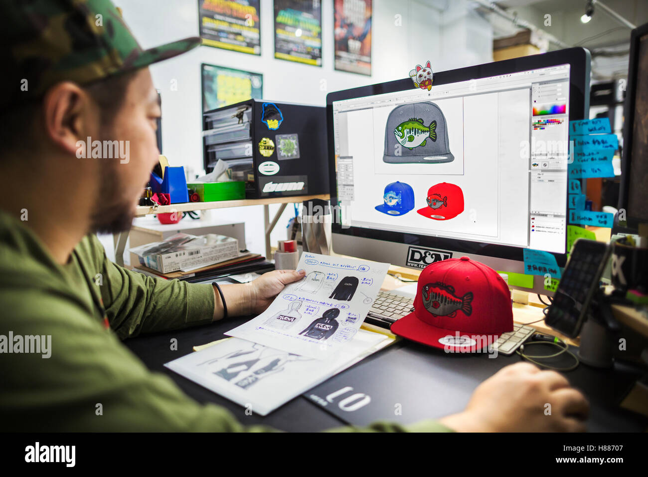A man, a designer working on screen creating designs for baseball caps. - Stock Image