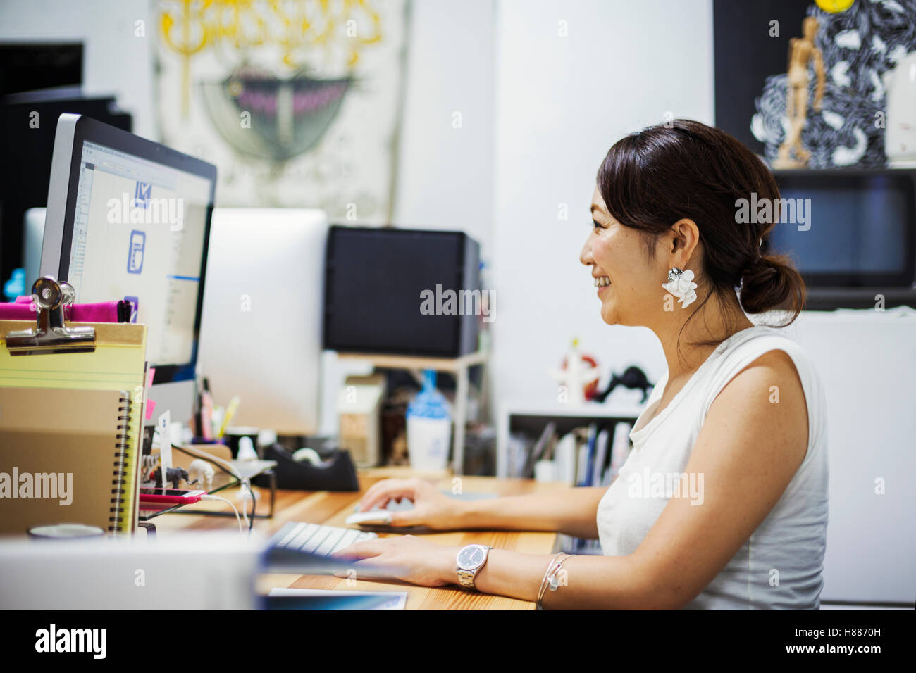 Design Studio. A woman sitting at a desk using a computer. - Stock Image