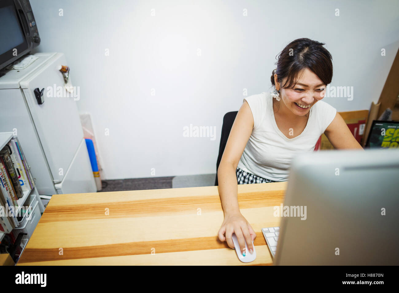 Design Studio. A woman working at a desk using a mouse and computer. - Stock Image