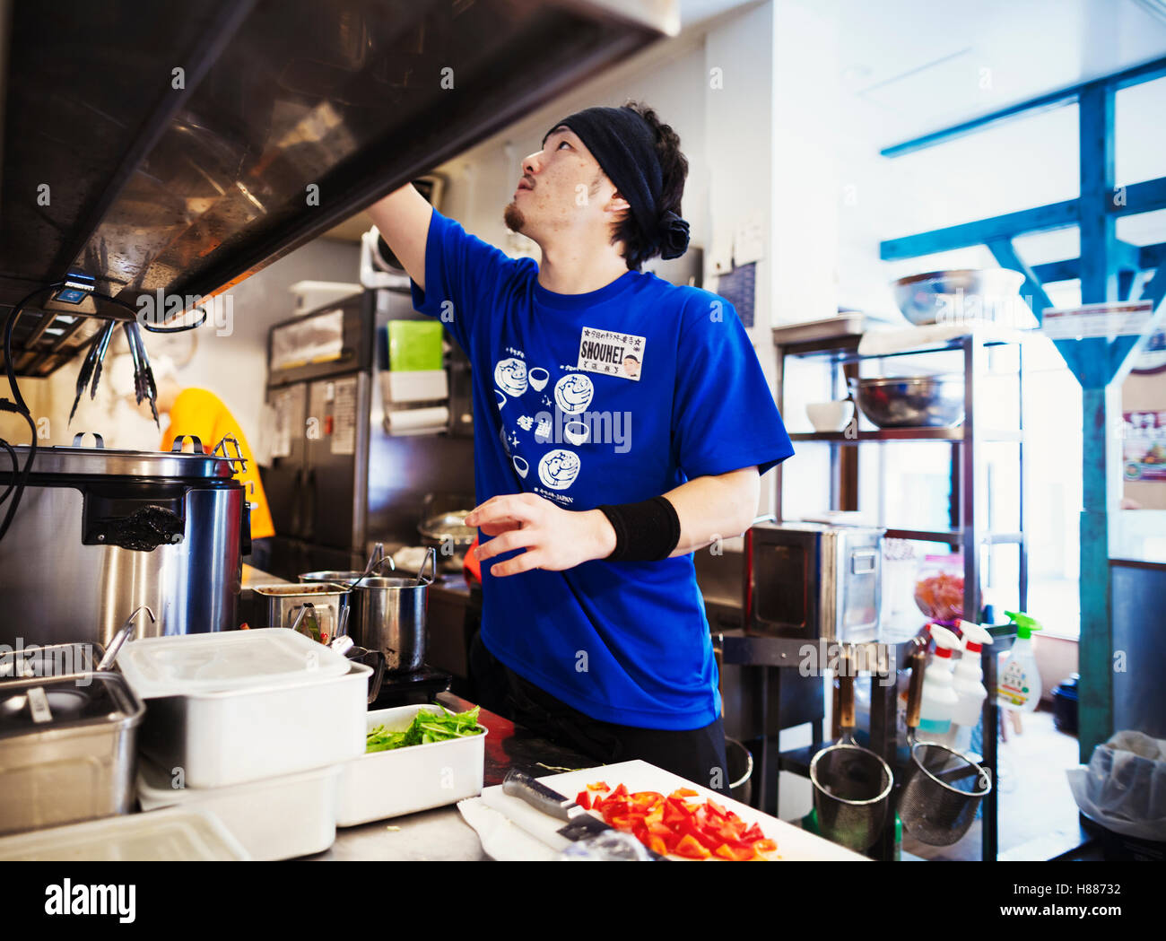 The ramen noodle shop. Staff in a small kitchen preparing food - Stock Image