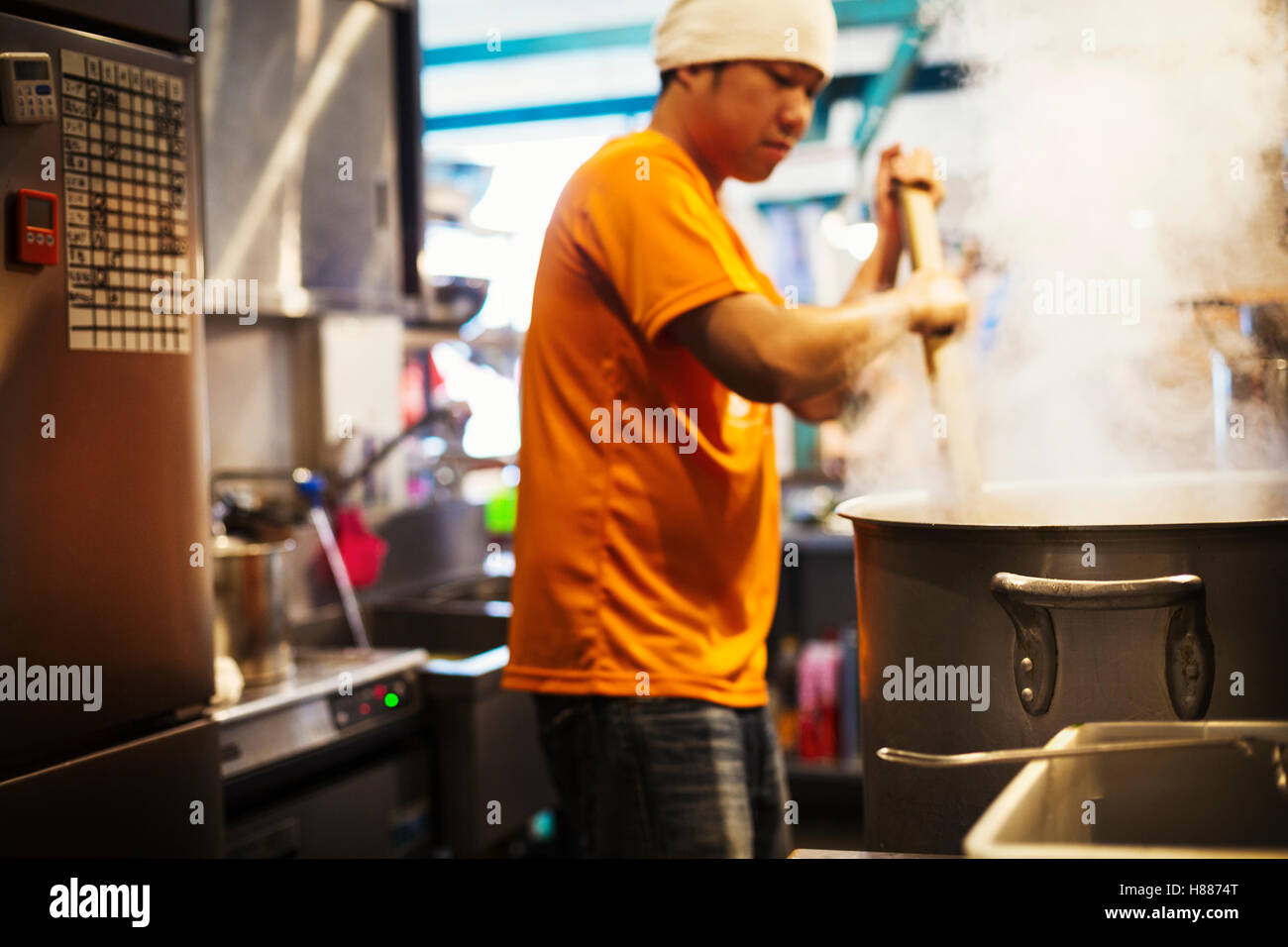 The ramen noodle shop. Staff preparing food in a steam filled kitchen. - Stock Image