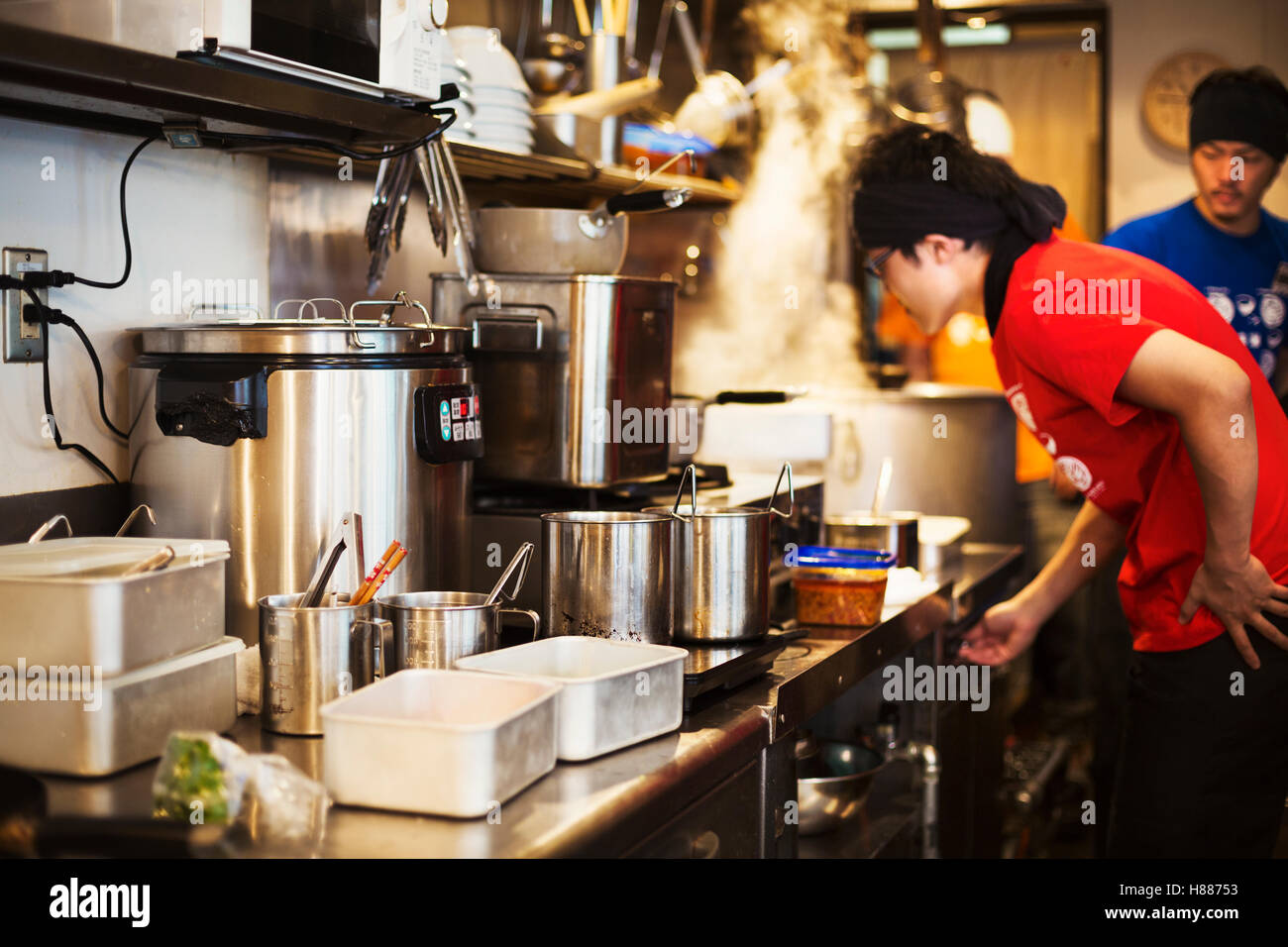 The ramen noodle shop.  Staff preparing food in a tiny kitchen - Stock Image
