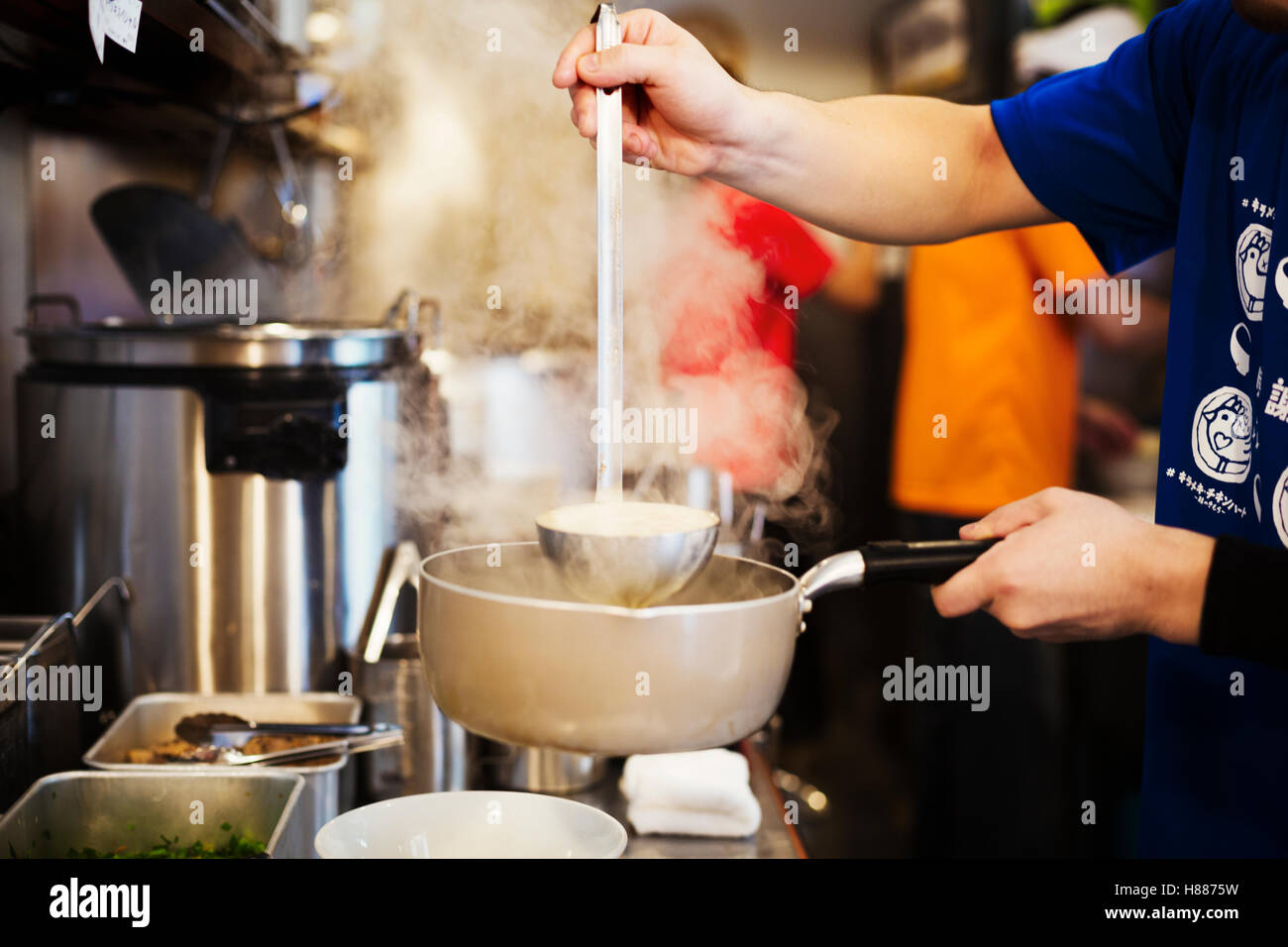 A ramen noodle shop kitchen. A chef preparing bowls of ramen noodles in broth, a speciality and fast food dish. - Stock Image