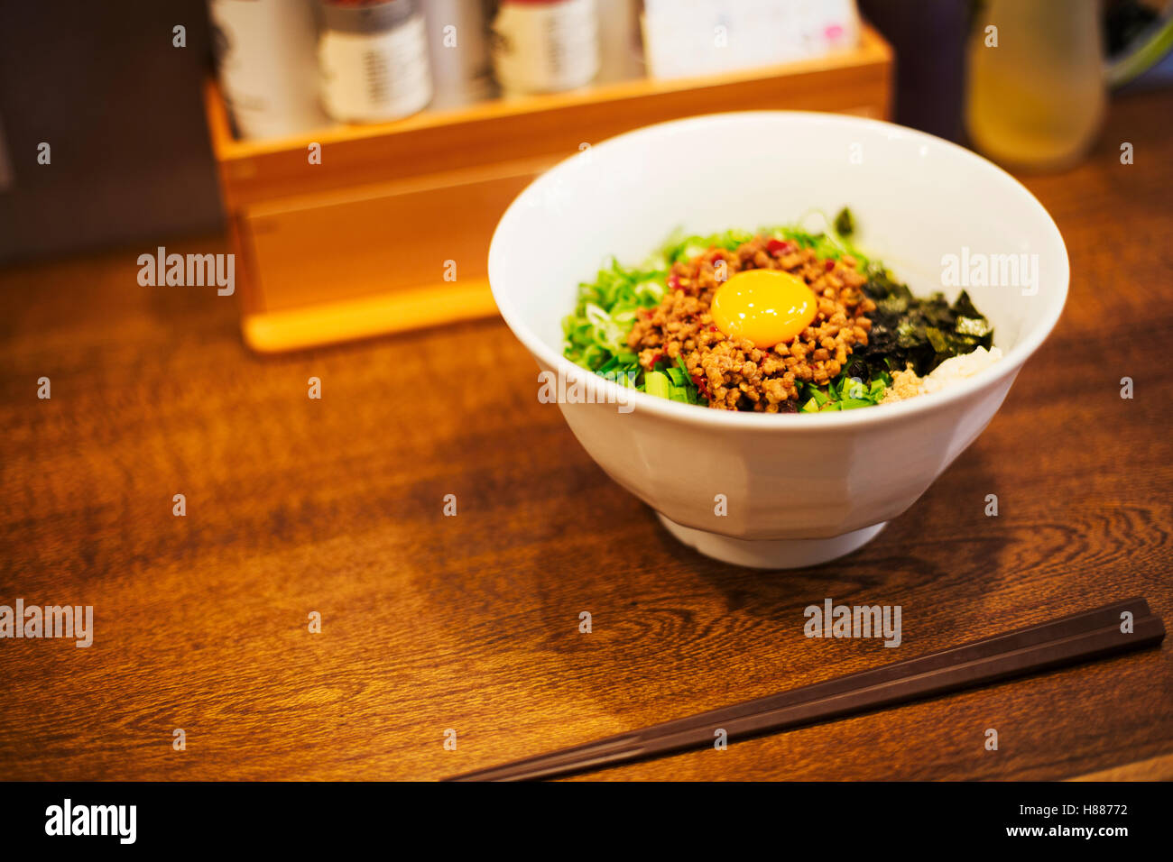 A ramen noodle shop. A white bowl of noodles with vegetables and an egg. Stock Photo