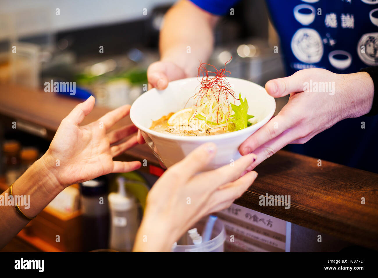The ramen noodle shop. A chef offering a white bowl of ramen noodle broth to a customer - Stock Image