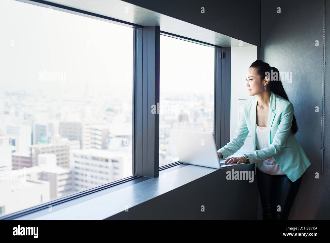 A business woman by a window with a view over the city, looking out. Laptop. Stock Photo