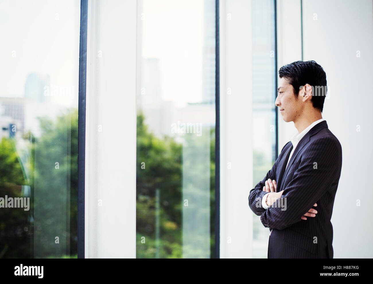 A businessman in the office, by a large window, looking out. - Stock Image