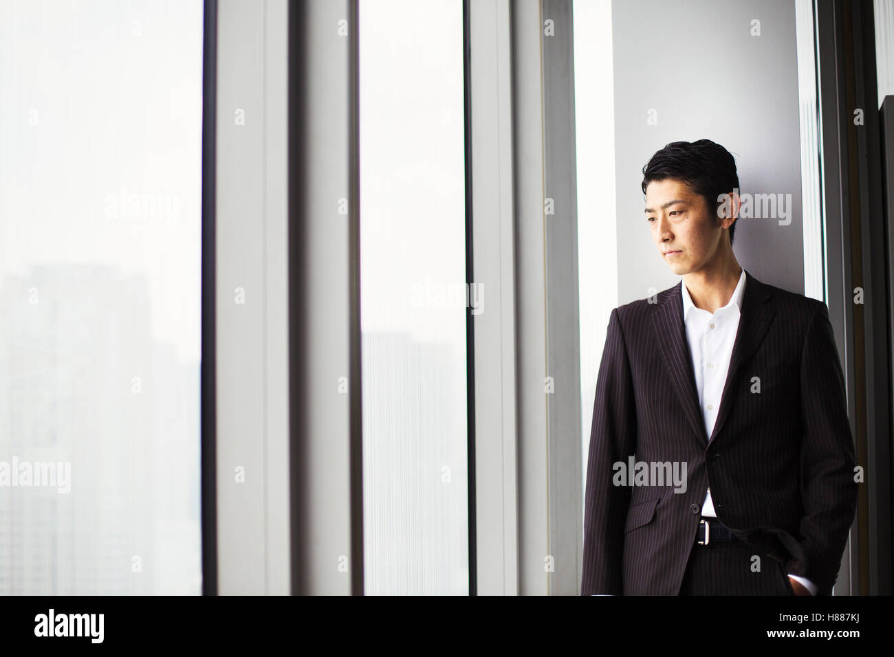 A businessman in the office, by a large window, looking over the city. - Stock Image