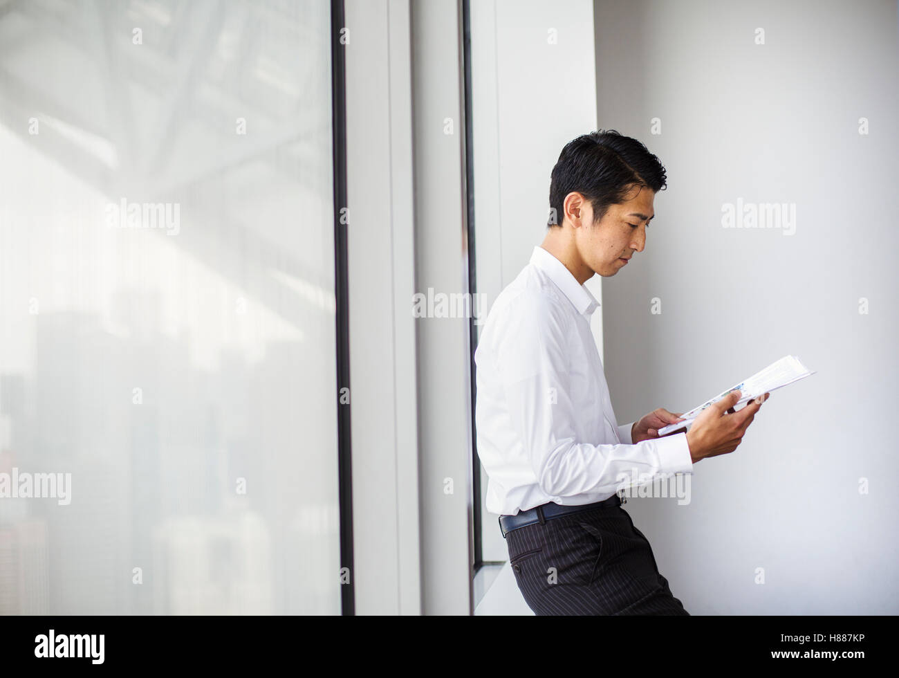 A businessman in the office, by a large window reading paperwork. leaning against the window sill. City office. - Stock Image