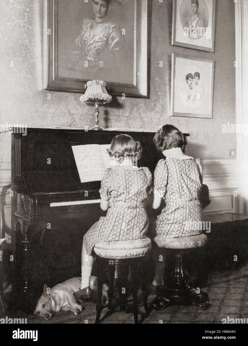 Princess Margaret, left, and Princess Elizabeth, future Queen Elizabeth II, right, playing a duet at the piano in - Stock Image