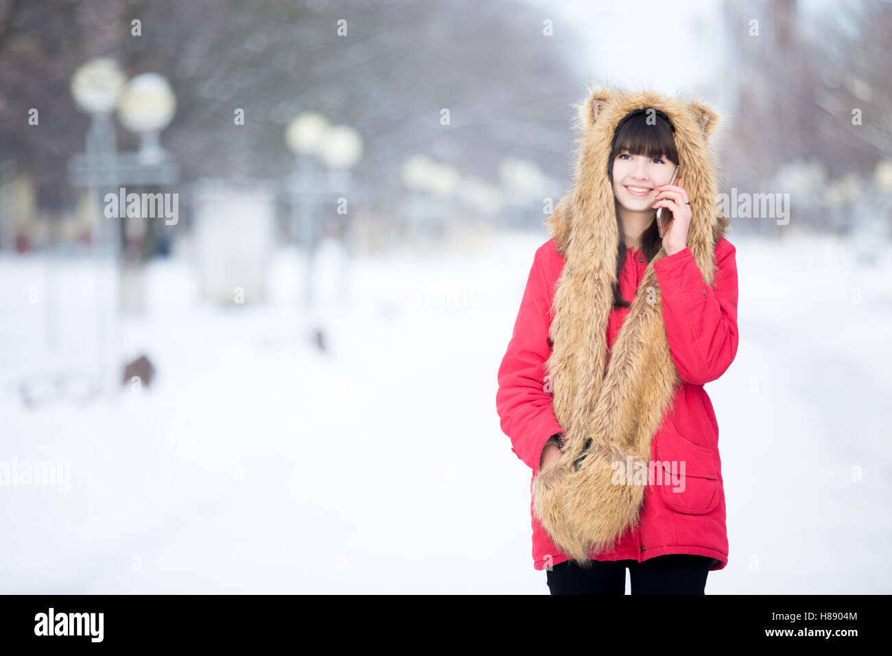 Young woman talking on phone outdoors in wintertime - Stock Image