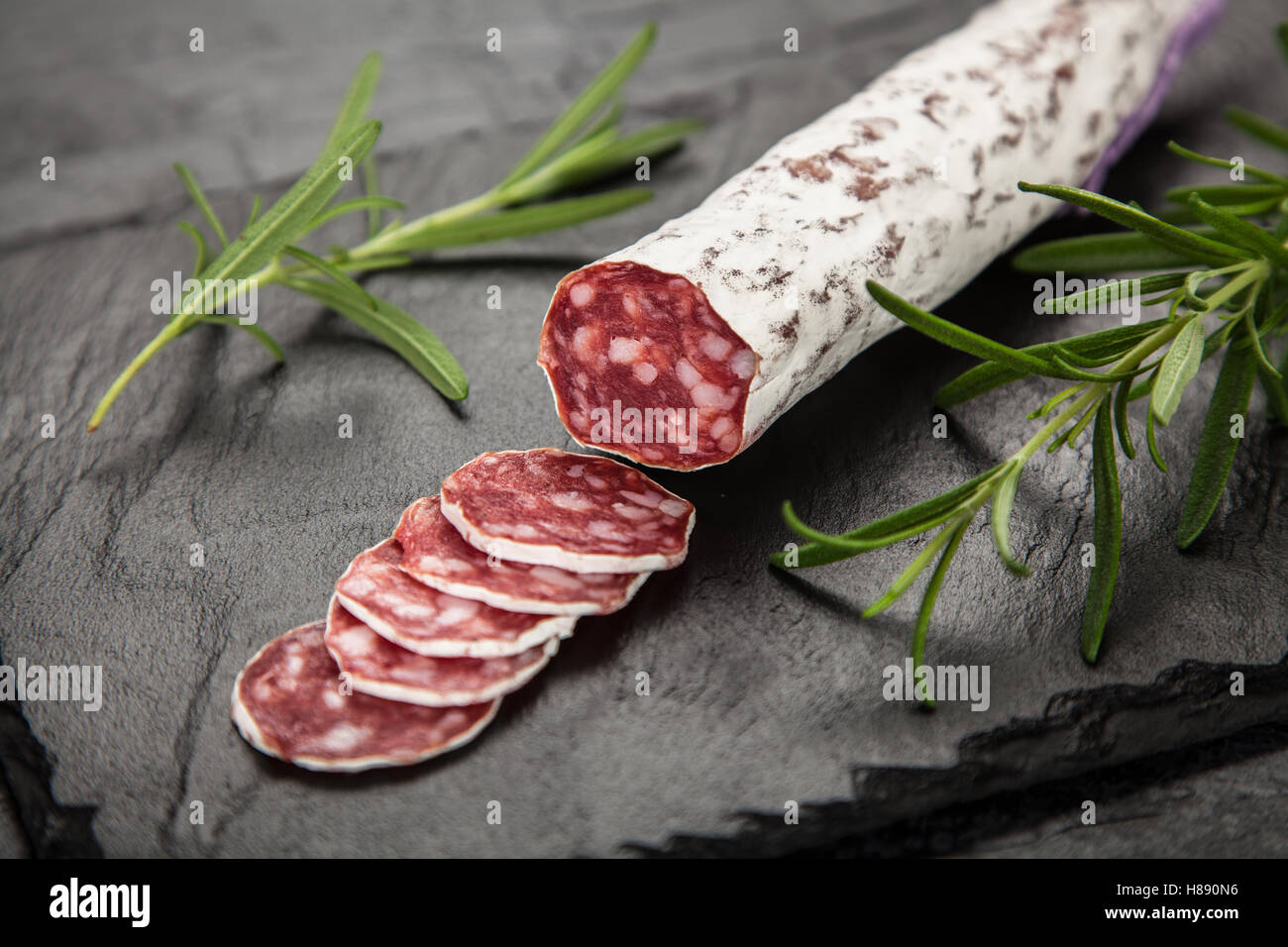 Salami on dark background - Stock Image