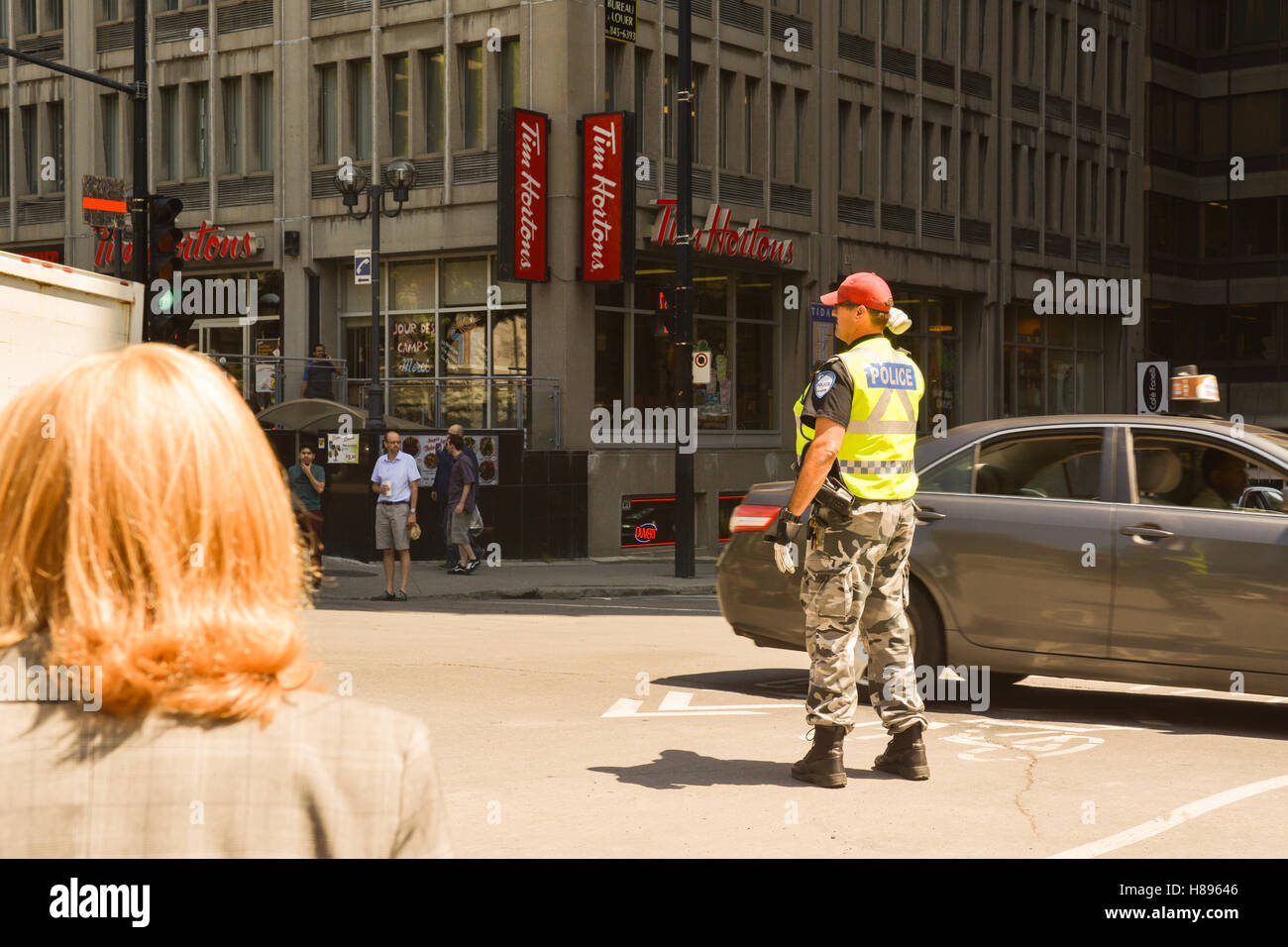 Montreal police officer directing managing traffic at intersection of Boulevard Robert-Bourassa and Rue Sherbrooke - Stock Image