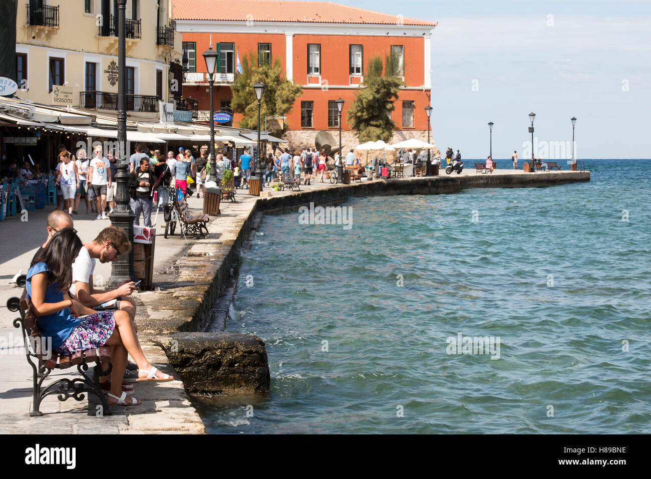 Greece, Crete, Chania, Venetian Port, Promenade to the western end of the harbour, the red building at the end is - Stock Image