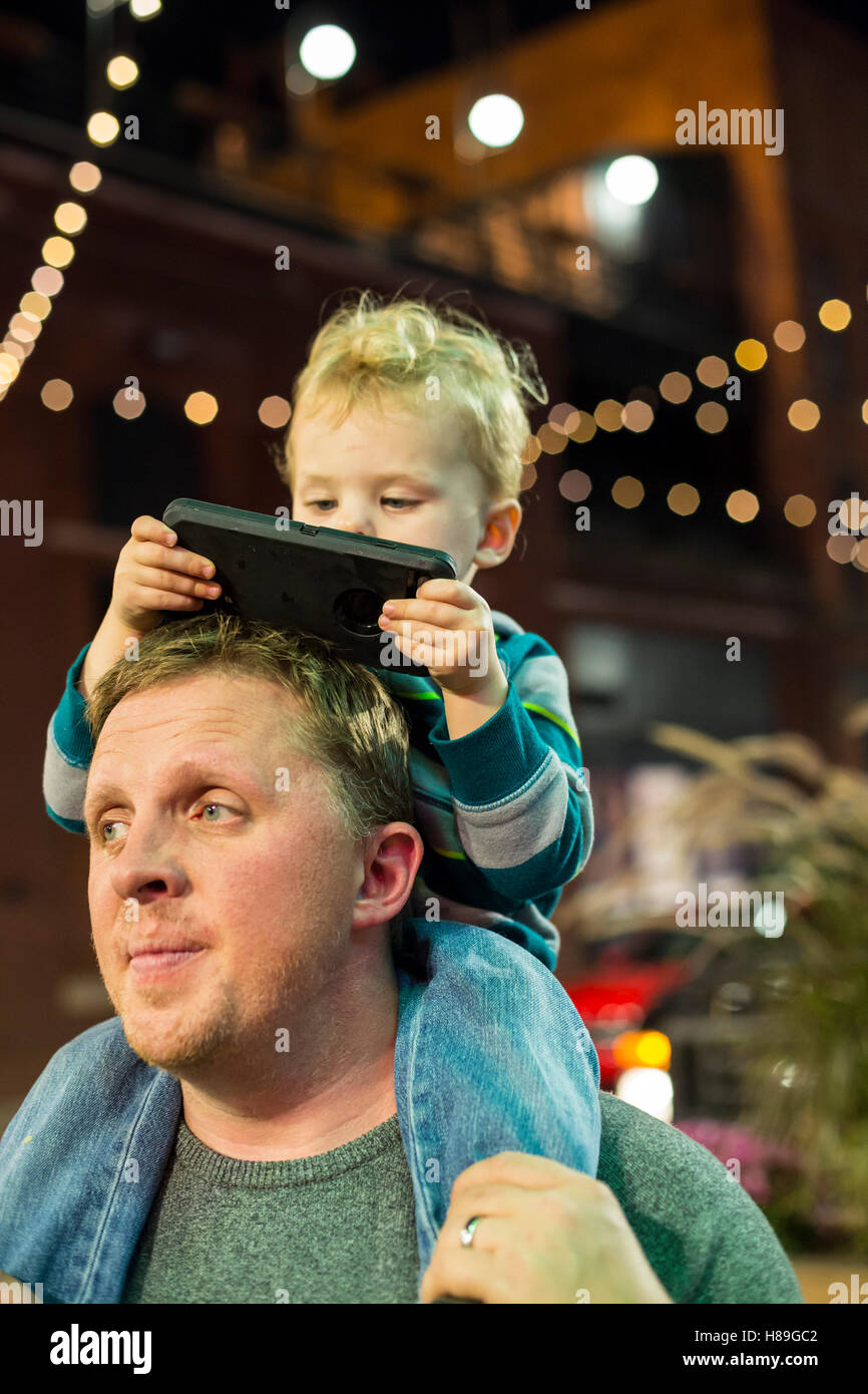 Detroit, Michigan - Two-year-old Adam Hjermstad Jr. looks at a cell phone while riding on the shoulders of his dad. - Stock Image