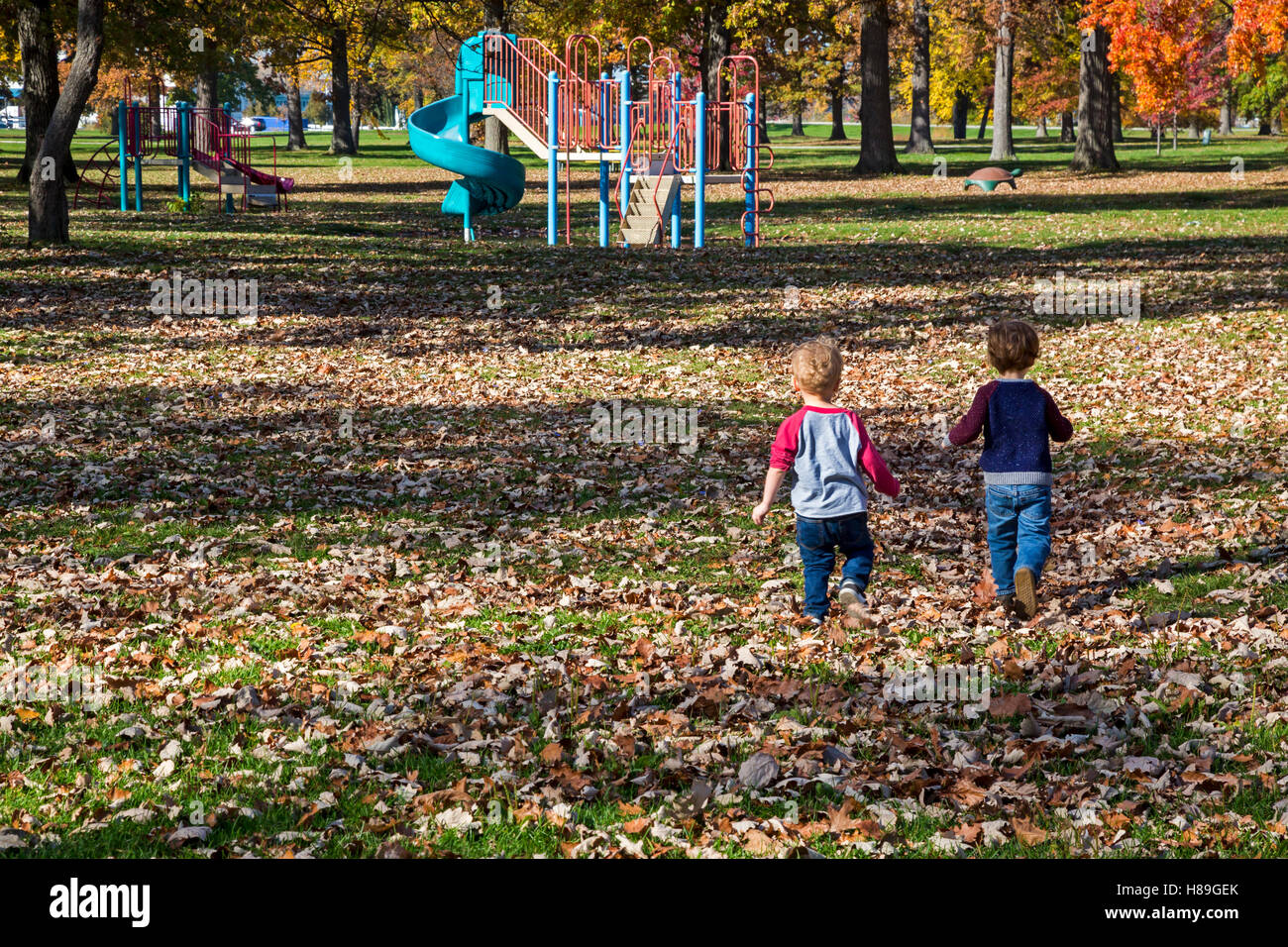Detroit, Michigan - Two- and three-year-old toddlers run towards a playground on Belle Isle. - Stock Image
