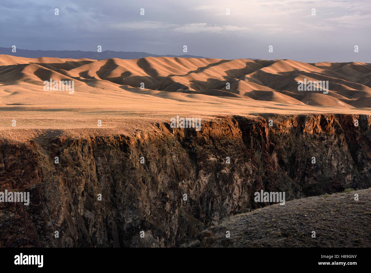 Sunset on rolling hills of Black Canyon on the Charyn river with Tien Shen mountains Kazakhstan - Stock Image