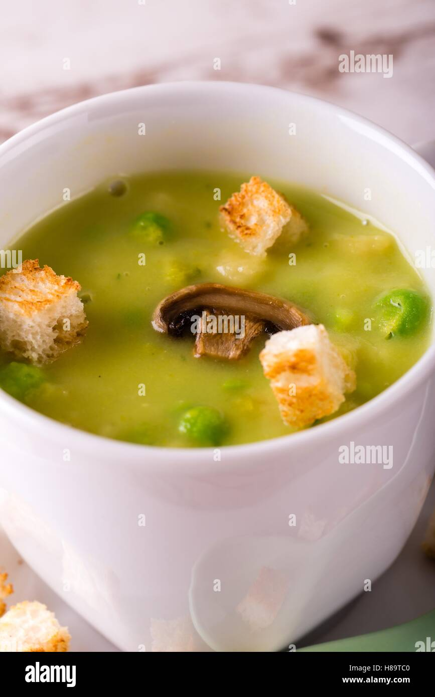 Vertical photo with detail of split pea soup. Green food in small white coffee cup with few bread croutons, peas Stock Photo