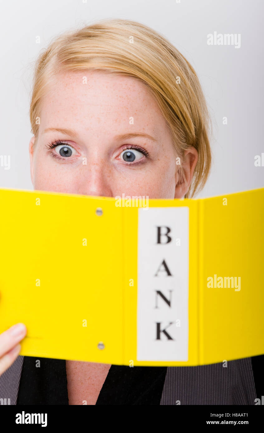 Horrified young woman looking at bank statements - Stock Image