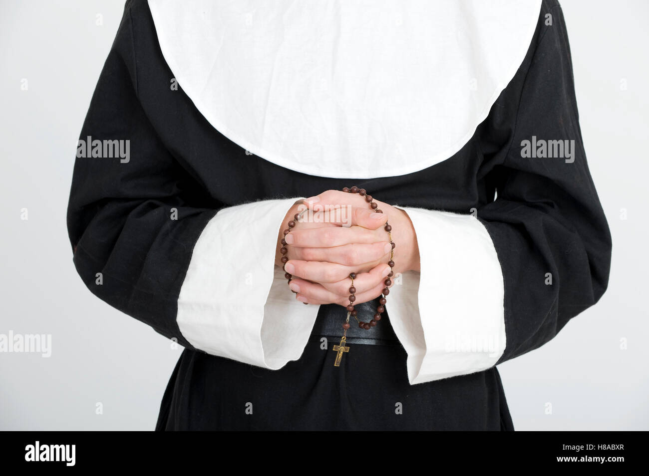 Nun praying the rosary - Stock Image