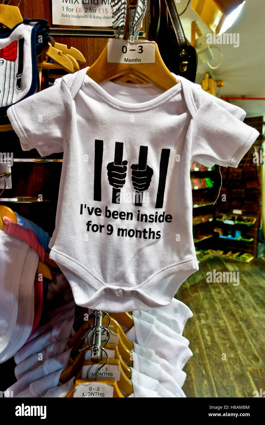 """White baby bodysuit hanging in a shop, reading """" I've been inside for  9 months"""" - Stock Image"""