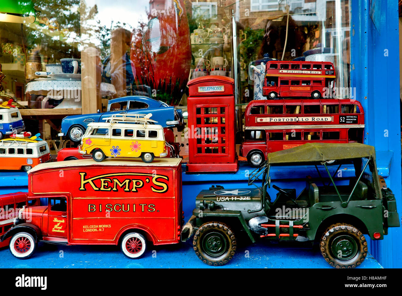 Many collectable old toy vehicles in bright colors on display in a window shop. Portobello Road market. London, - Stock Image