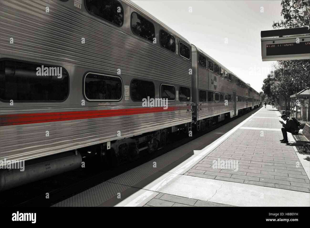 Long train with red stripe at platform in black and white Stock Photo