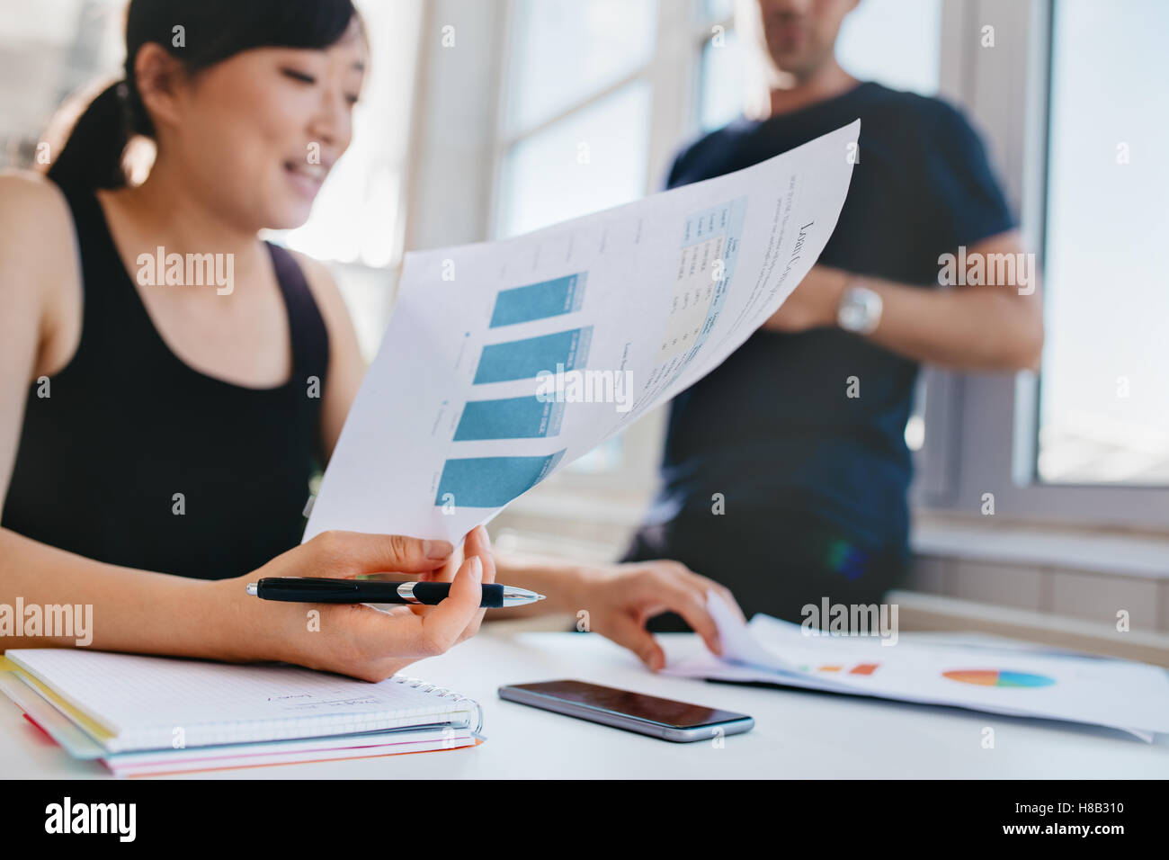 Woman doing financial analysis at office with male colleague standing in background. Asian female holding documents - Stock Image