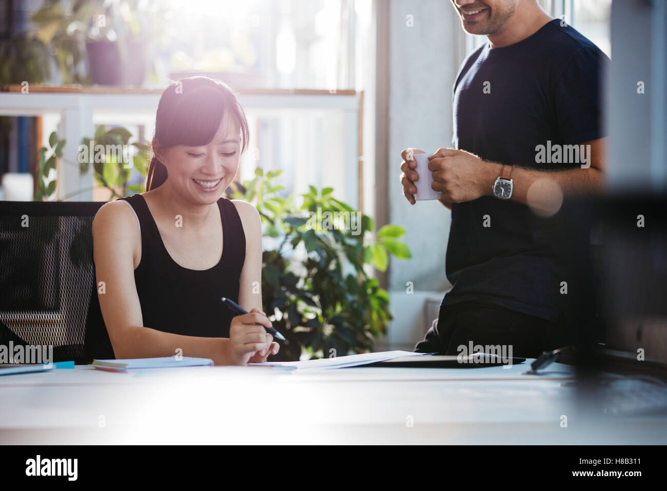 Shot of smiling young woman sitting at her desk working with male colleague standing by. Business people at work - Stock Image