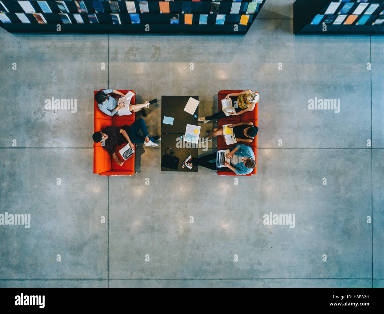 Top view of university students sitting in a library with books and laptop. Young people studying together at college - Stock Image