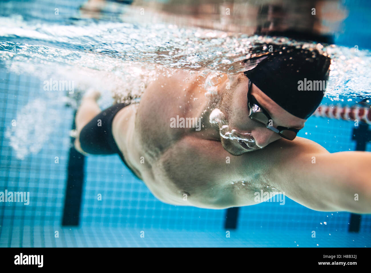 Professional male swimmer practising in swimming pool. Underwater shot of young sportsman swimming in pool. Stock Photo