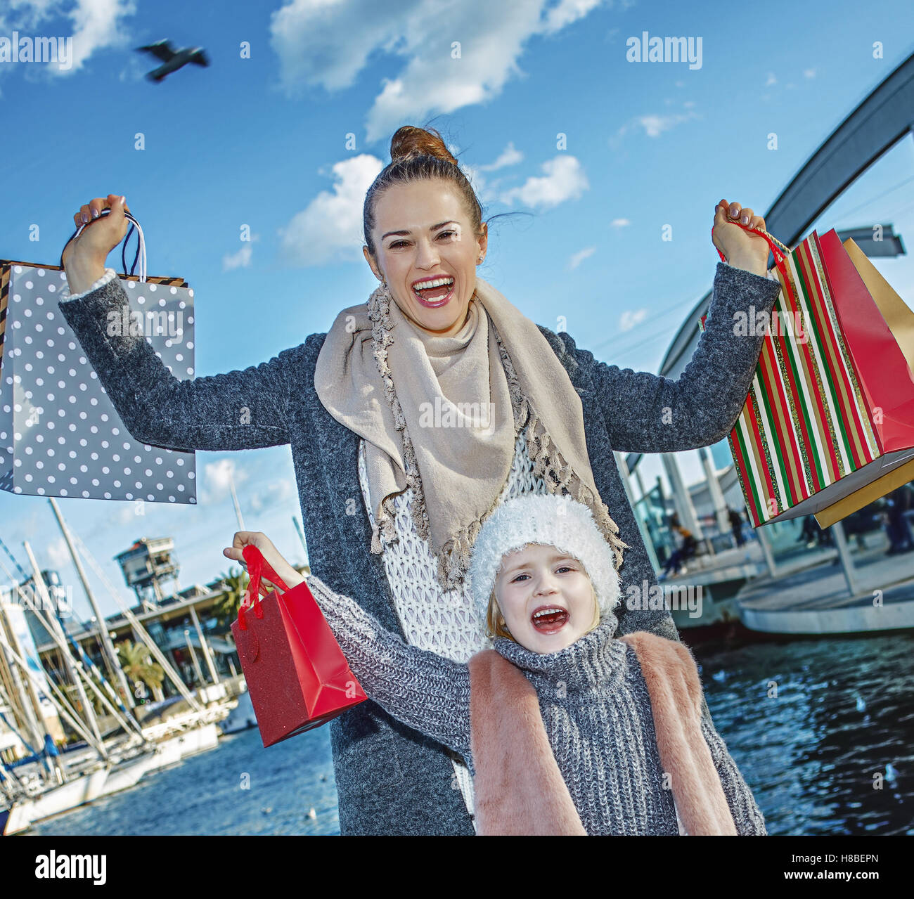 in Barcelona for a perfect present. smiling modern mother and child with shopping bags on embankment in Barcelona, - Stock Image