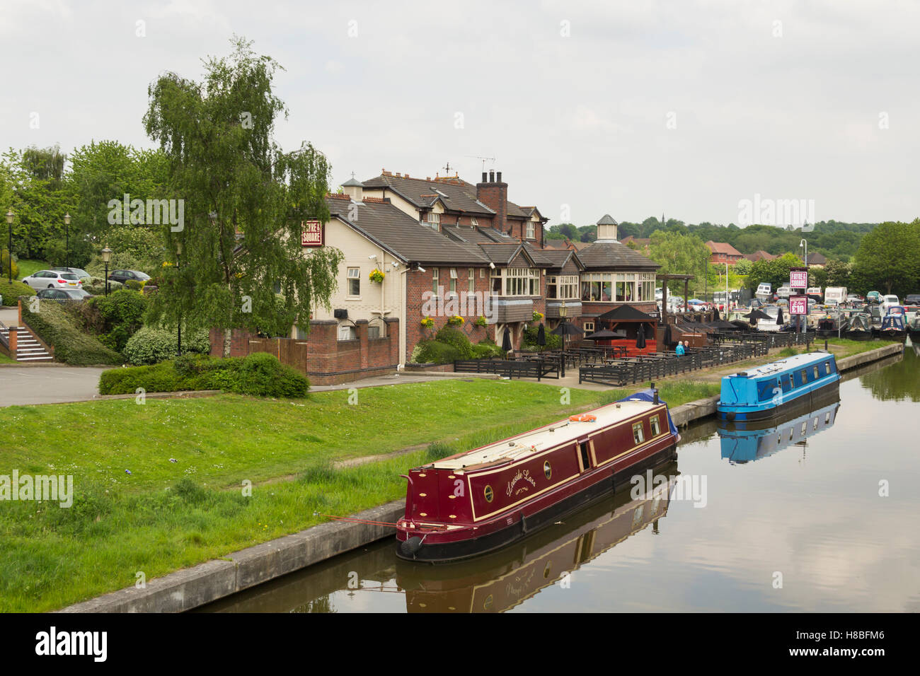 May 2016, Boothstown, Greater Manchester, UK. Narrowboats moored outside The Moorings pub on Boothstown marina on - Stock Image