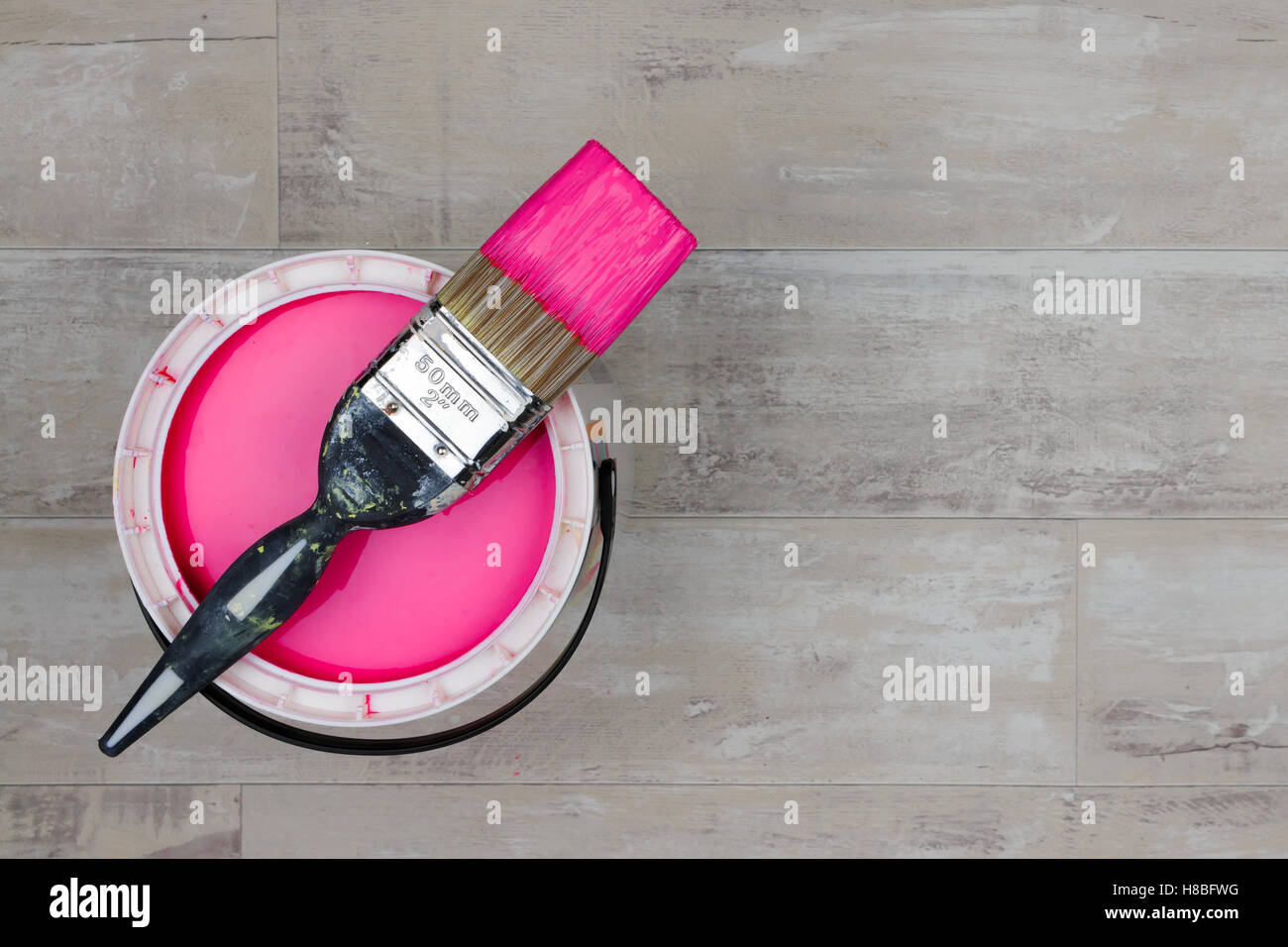 Can of magenta Paint with a loaded brush stood on a shabby style wood floor - Stock Image