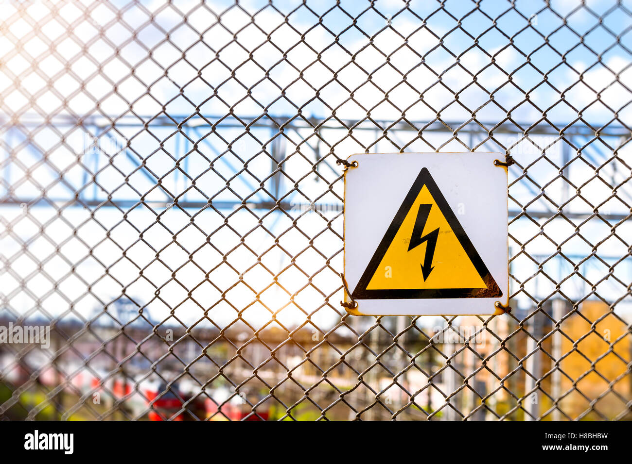 Yellow Warning Sign With High Voltage Symbol Hanging On The Stock