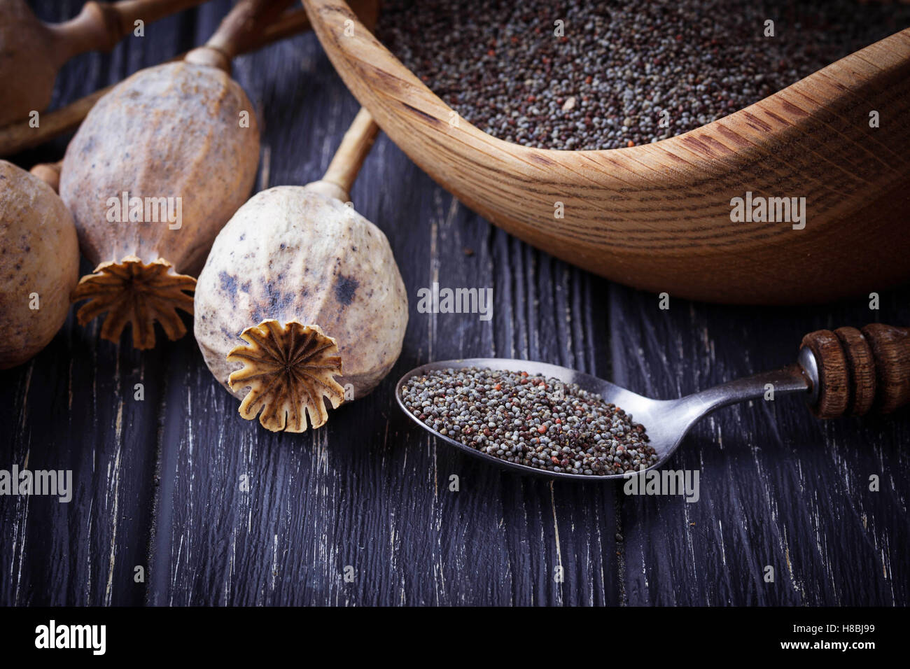 Poppy seeds and heads on wooden background. Selective focus - Stock Image