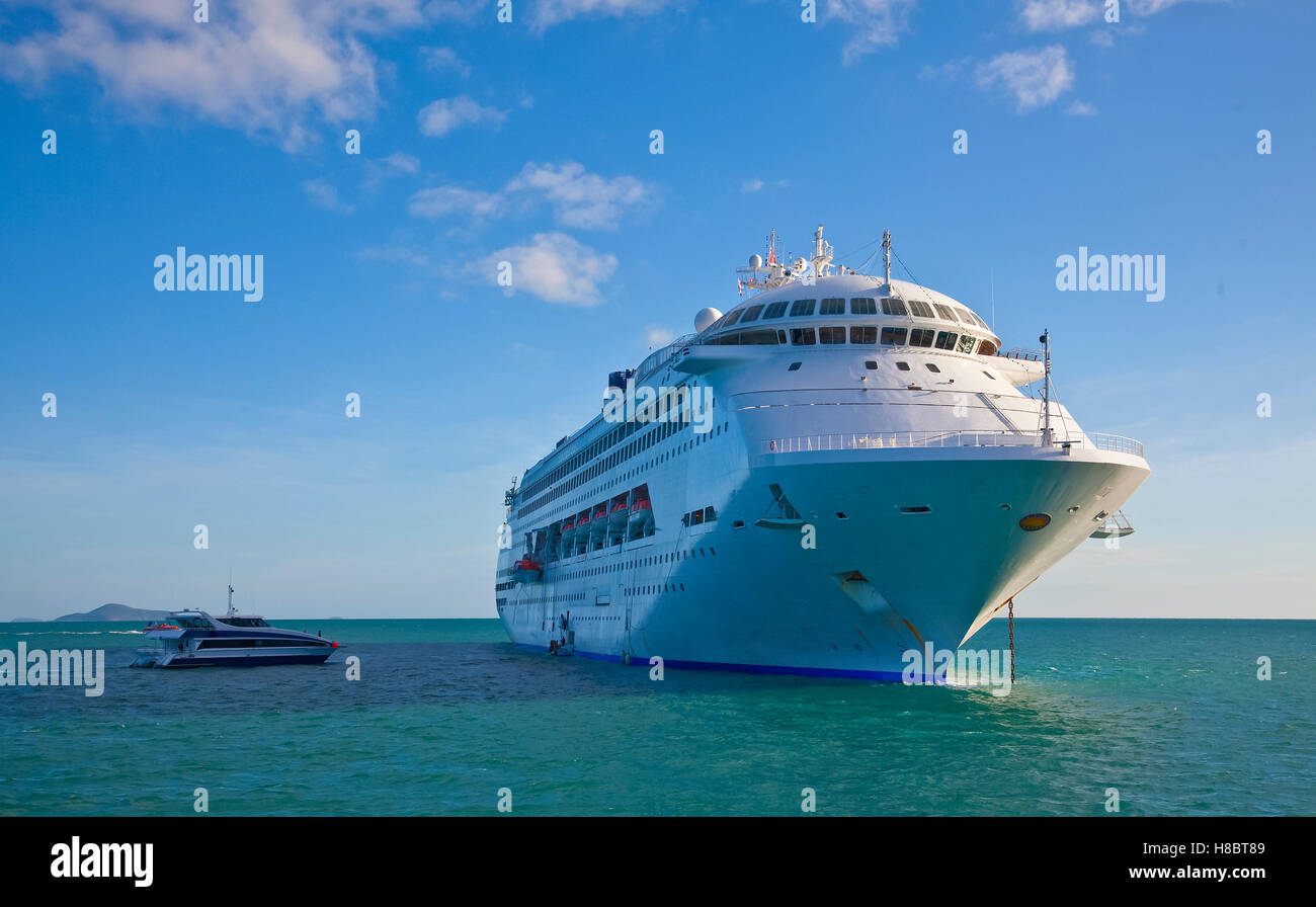 Cruise ship anchored near Hamilton Island as tourists re-embark after a day of sight seeing - Stock Image